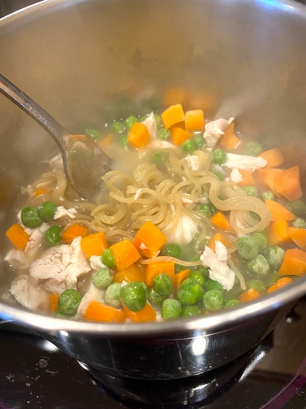 chicken and vegetables added to the pot of cooked ramen noodles
