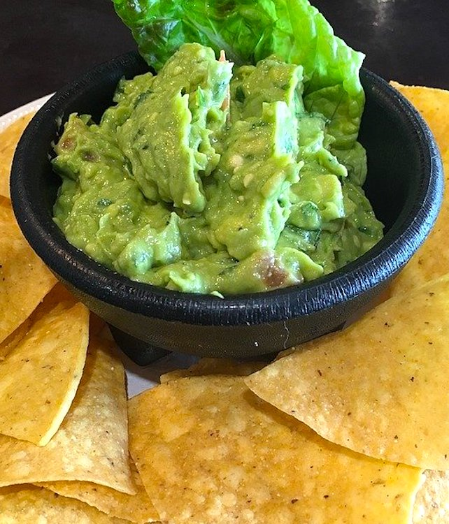 guacamole and chips on a taco bar