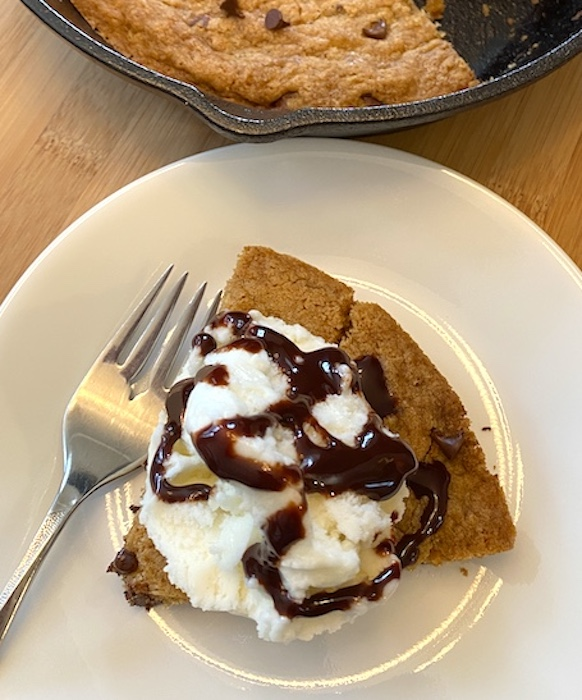 mini skillet cookie topped with vanilla ice cream and chocolate syrup