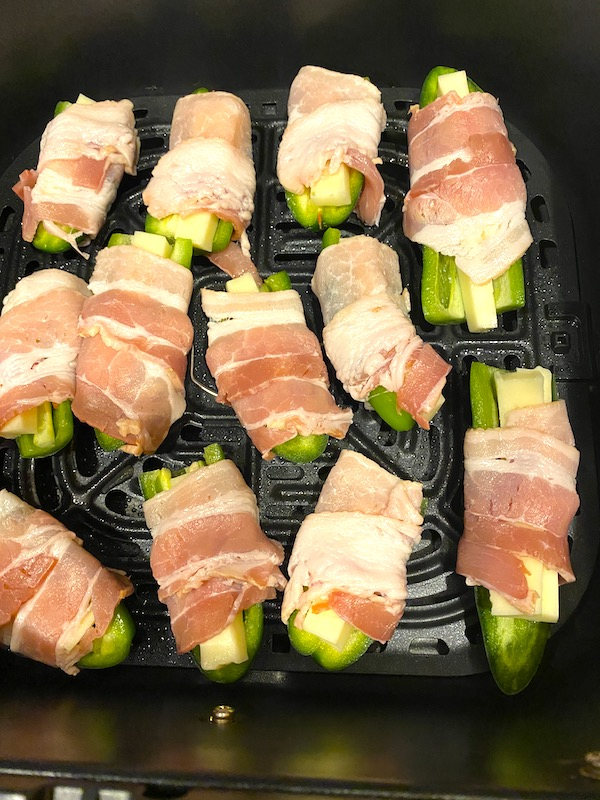 bacon wrapped cheese stuffed peppers in an air fryer basket