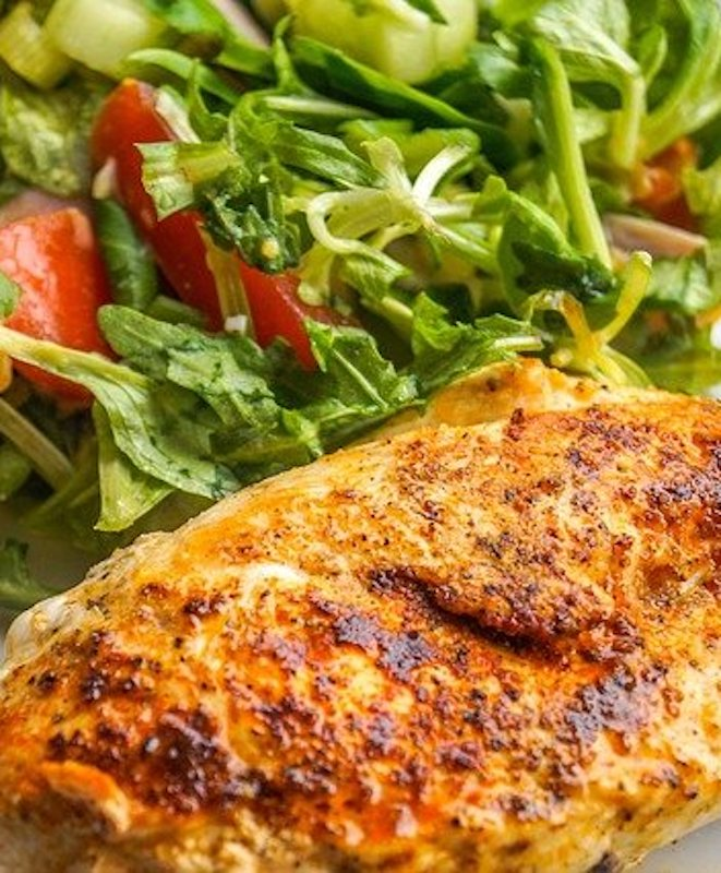 air fried boneless chicken breast on a plate with salad