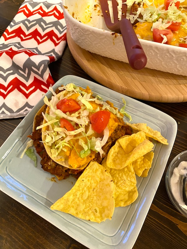 beef and bean enchilada on a plate next to a casserole dish