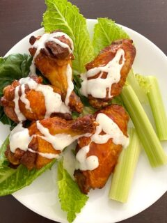 reheated chicken wings on a plate with lettuce and celery
